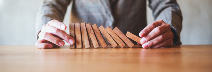 Closeup image of a businessman try to holding wooden block while falling for business concept