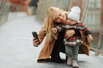 Mother and her little child taking selfie while walking on the street.