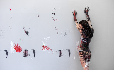 Woman in underwear, sportswear, young and sexy, artistically abstract painted with black, red, white, paint, rolls off in front of wall in studio and leaves colorful color prints, copy space.