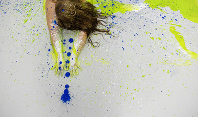 Head and hands of a plus size, fat, overweight, chubby woman in blue, green, yellow color painted decorative. View from above, creative expressive abstract body painting art, copy space.