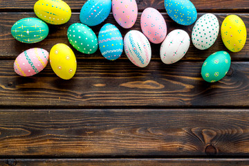 Colorful Easter eggs frame on dark wooden background top-down copy space