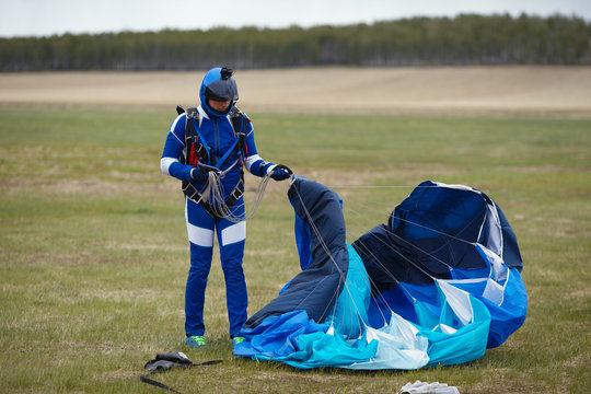 Skydiver after landing folds the canopy of a parachute close-up. Parachute equipment.