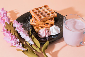 Sweet delicious dessert, homemade baked goods for breakfast. Belgian European soft waffles on a black plate, meringue, fruit berry yogurt