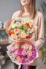 Two Beautiful bouquets of mixed flowers in womans hands. the work of the florist at a flower shop. Delivery fresh cut flower. European floral shop.