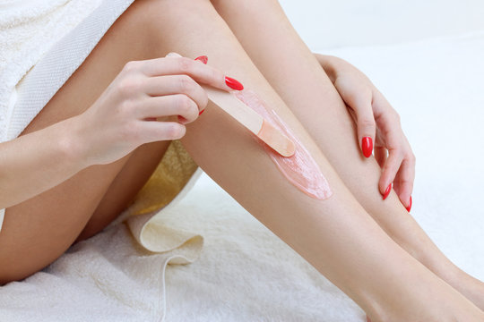Woman waxing her legs with wooden stick.