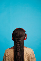 Vertical back view shot of unrecognizable Black woman with long hair wearing red headphones listening to music, blue background