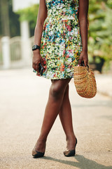 Unrecognizable Black woman with slim legs wearing beautiful summer dress standing outdoors, vertical shot