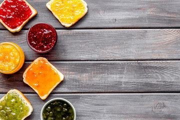 Toast with colorful fruit jam frame on dark wooden background frame copy space