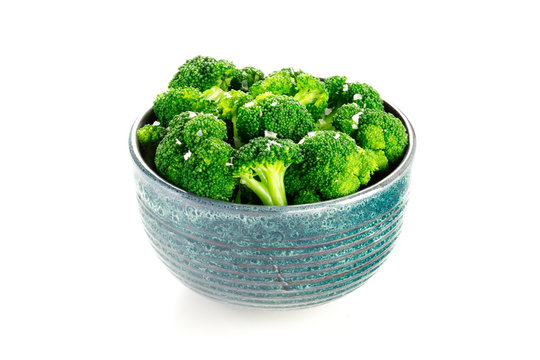 A bowl of cooked broccoli with salt on a white background