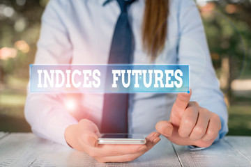 Handwriting text Indices Futures. Conceptual photo cashsettled futures contract on the value of a stock Female business person sitting by table and holding mobile phone