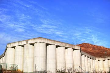 円柱を並べたコンクリートの白い擁壁と雲のある青空