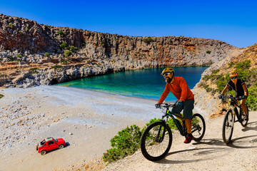 Wall Mural - Cycling woman and man on electric bikes to wild beach with turquoise water and off-road  access . Couple cycling MTB enduro trail track. Outdoor sport activity.