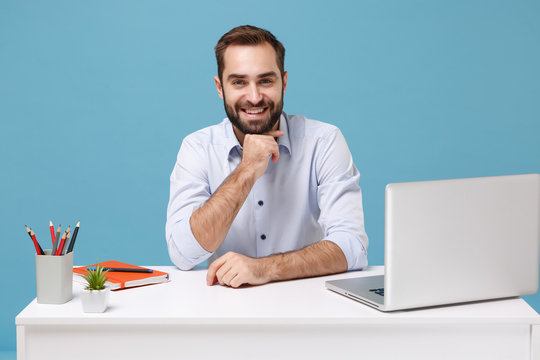Smiling young bearded man in light shirt sit work at white desk with pc laptop isolated on blue background. Achievement business career lifestyle concept. Mock up copy space. Put hand prop up on chin.