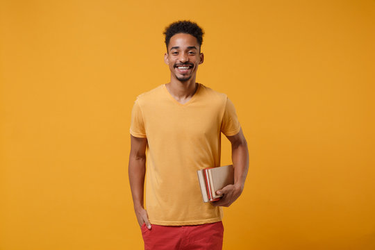 Smiling young african american guy in casual t-shirt posing isolated on yellow orange wall background, studio portrait. People lifestyle concept. Mock up copy space. Hold in hands books, notebooks.