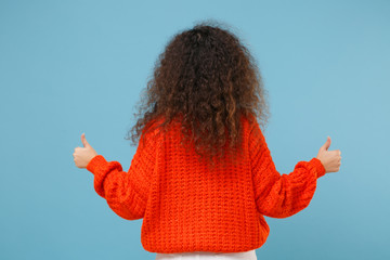 Back rear view of young african american girl in casual orange knitted clothes isolated on pastel...