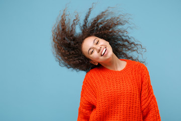 Smiling young african american girl in casual orange knitted clothes isolated on pastel blue wall background studio portrait. People lifestyle concept. Mock up copy space. Having fun with flying hair.