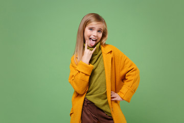 Funny little blonde kid girl 12-13 years old in yellow coat posing isolated on pastel green...