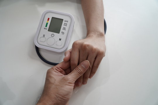 Monitoring blood pressure of patients using upper arm blood pressure monitor in the clinic examination room.