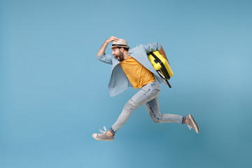 Side view of excited traveler tourist man in yellow clothes isolated on blue background. Male passenger traveling abroad on weekends. Air flight journey concept. Jumping like running, hold suitcase. Fotomurales