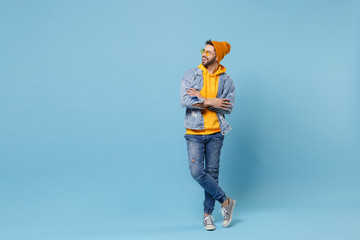 Funny young hipster guy in fashion jeans denim clothes posing isolated on pastel blue background studio portrait. People lifestyle concept. Mock up copy space. Holding hands crossed, looking aside.