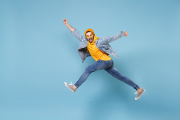 Side view of crazy young hipster guy in fashion jeans denim clothes posing isolated on pastel blue background. People lifestyle concept. Mock up copy space. Jumping spreading hands and legs screaming. Wall mural