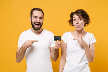 Excited young couple friends bearded guy girl in white blank empty t-shirts isolated on yellow...