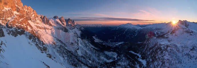 Aerial, panoramic winter view on Pale di San Martino mountains and valley covered in snow. Vezzana, Dolomites. Red rocks lit by setting sun against blue sky. San Martino di Castrozza, Italy.