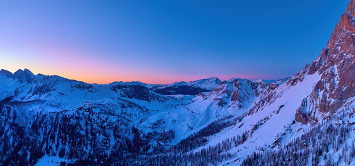 Aerial, colorful panoramic winter view on Pale di San Martino mountains covered in snow. Passo Rolle view, evening mountainscape, orange and dark blue sky. Dolomites, San Martino di Castrozza, Italy.
