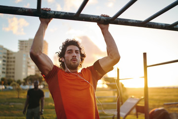 Portrait of a young crossfit sportsman exercising on bar, doing pull-ups for arms and back muscles at the outdoor gym park Fotomurales