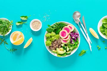 Vegan lunch bowl with quinoa, cucumber, green peas, radish, romanesco broccoli, red cabbage, avocado, spinach and arugula salad, healthy eating, vegetarian food concept, veggie detox antioxidant diet