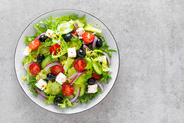 Salad with fresh raw vegetables, cucumber, tomato, olive, onion, lettuce and feta cheese, greek cuisine, healthy food, top view.