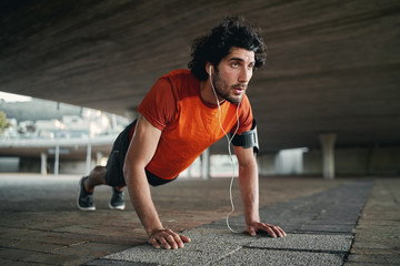 Attractive fit man listening to music in earphone doing push-ups exercises during workout outdoors - man showing perseverance and determination