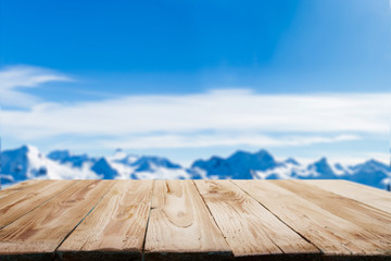 Empty wooden surface on blurry background of snowy mountainous area on winter day and blue sky.