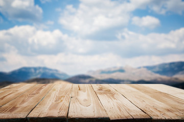 Empty wooden surface on blurry background of snowy mountainous area on winter day and blue cloudy sky.