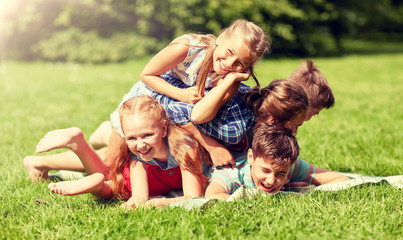 friendship, childhood, leisure and people concept - group of happy kids or friends playing and having fun in summer park