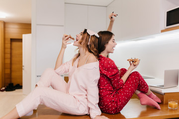 Attractive female models in cute socks sitting on wooden table in kitchen. Refined girls in pajamas...