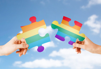 homosexual and lgbt concept - hands matching puzzle pieces with gay flag colors over blue sky and clouds background