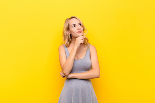 young blonde woman feeling thoughtful, wondering or imagining ideas, daydreaming and looking up to copy space against orange wall