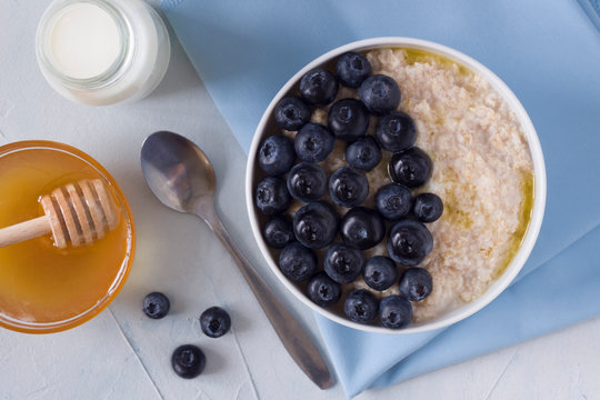 oatmeal with butter, milk, honey and blueberries on the table