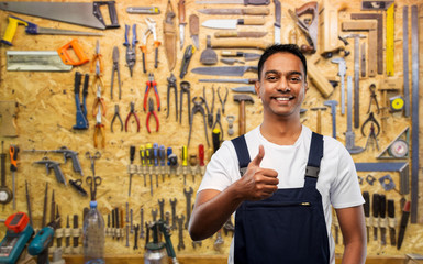 profession, construction and building - happy smiling indian worker or builder showing thumbs up over working tools on wall at workshop background Wall mural