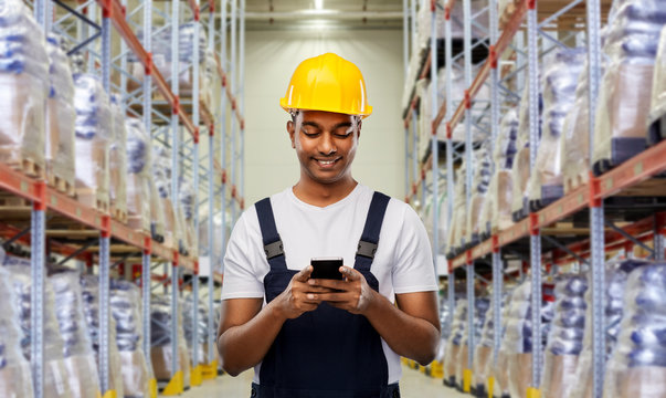 logistic business, technology and people concept - happy smiling indian loader or worker in helmet with smartphone over warehouse background