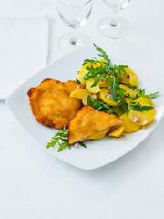 Hühnchen Cordon Bleu mit Kartoffelsalat auf weißem Hintergrund
