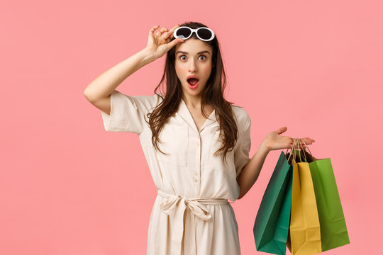 Lets go shopping. Amused and excited female shoppaholic having fun browsing through city malls, holding shop bags, taking-off glasses seeing exactly what been looking for, pink background