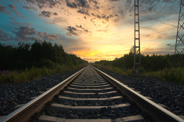 Long railroad track leading into a beautiful sunset.