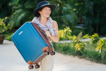 Beautiful girl in a hat holds a larger blue suitcase. Travel and vacation concept.