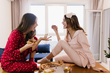 Inetersted girls talking around and eating cheese pizza. Indoor photo of lovable dark-haired ladies...