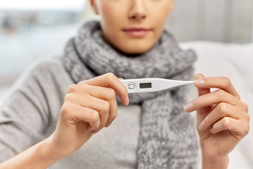 people, health and fever concept - close up of sick woman in scarf measuring temperature by thermometer at home