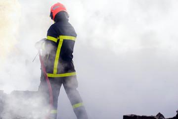 firefighter in smoke muffling a fire in close up