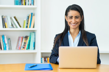 Pretty latin american mature businesswoman with blazer at computer Wall mural