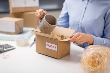delivery, mail service, people and shipment concept - close up of woman packing mug to parcel box with straw filler at post office